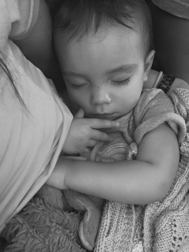 sleeping toddler on mom's lap after breastfeeding