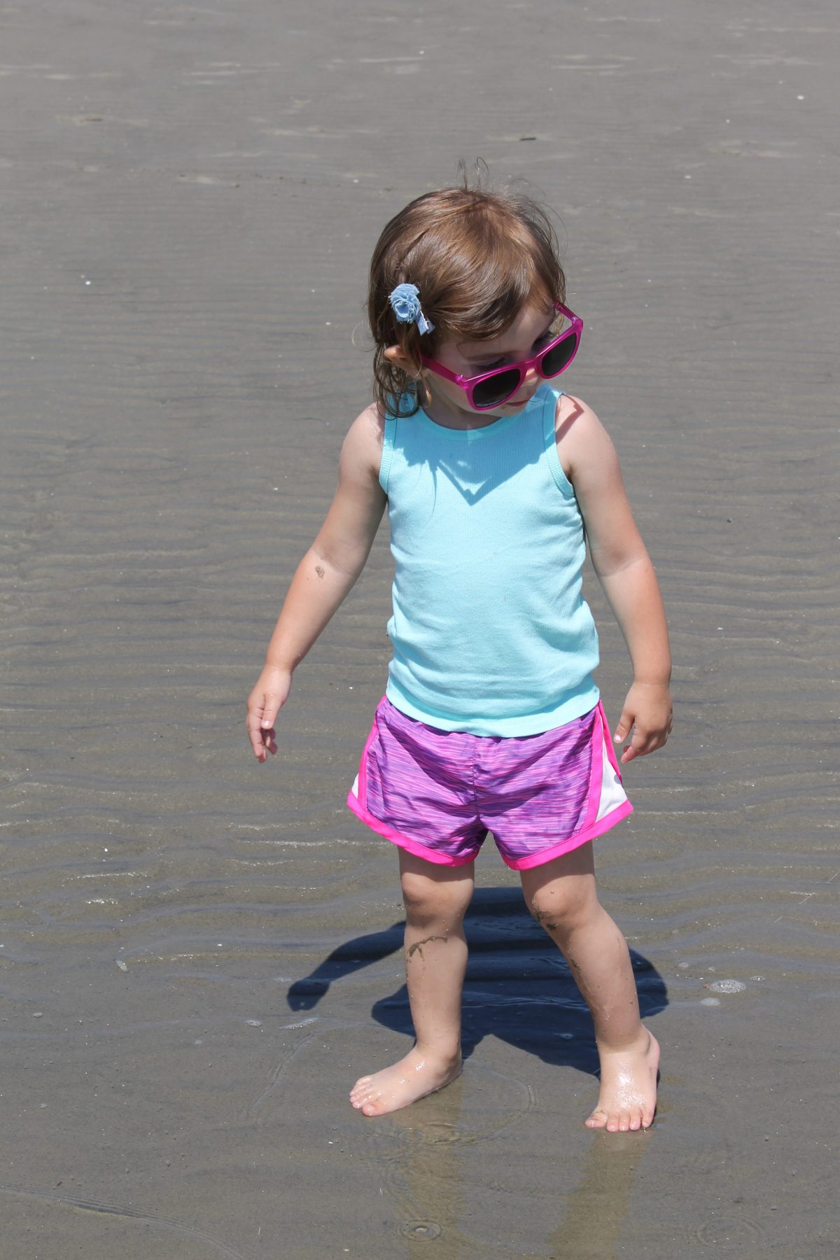 Toddler wearing pink sunglasses, blue tank, pink shorts on Old Saybrook Beach