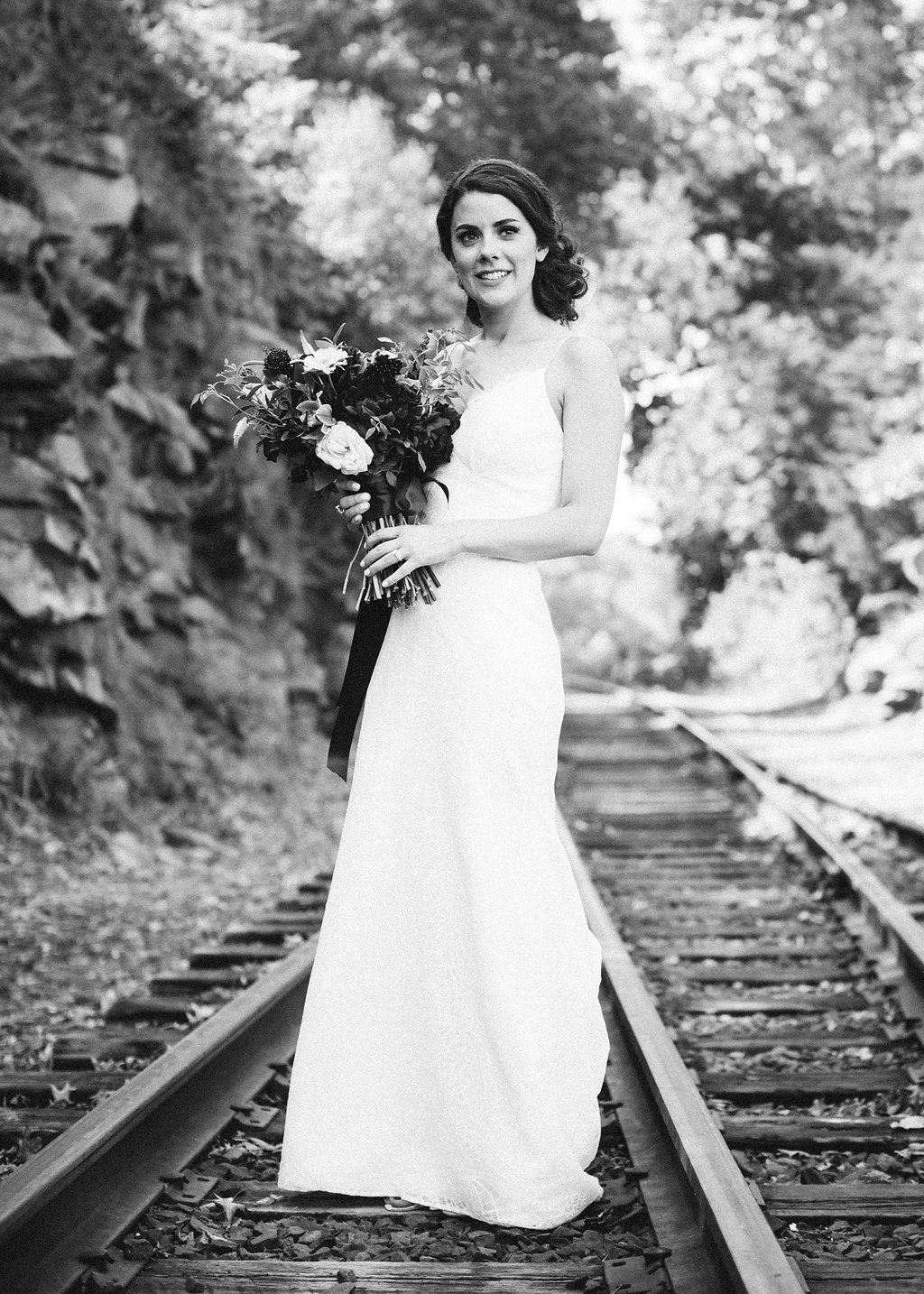 bride in wedding dress on railroad tracks