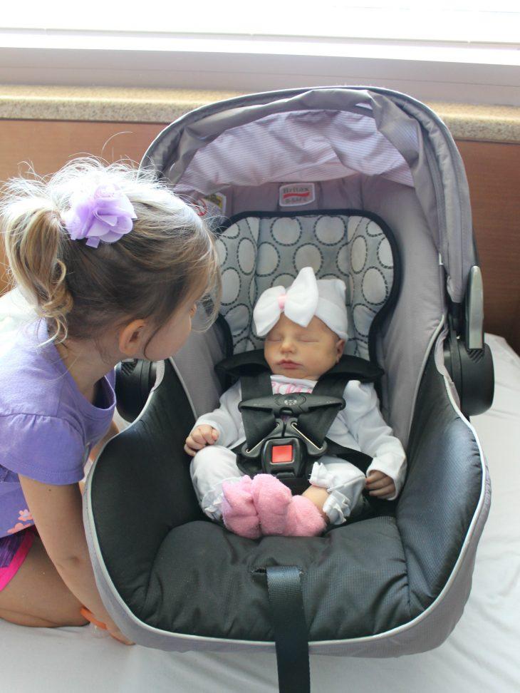 Little girl peeking in at a newborn in a car seat
