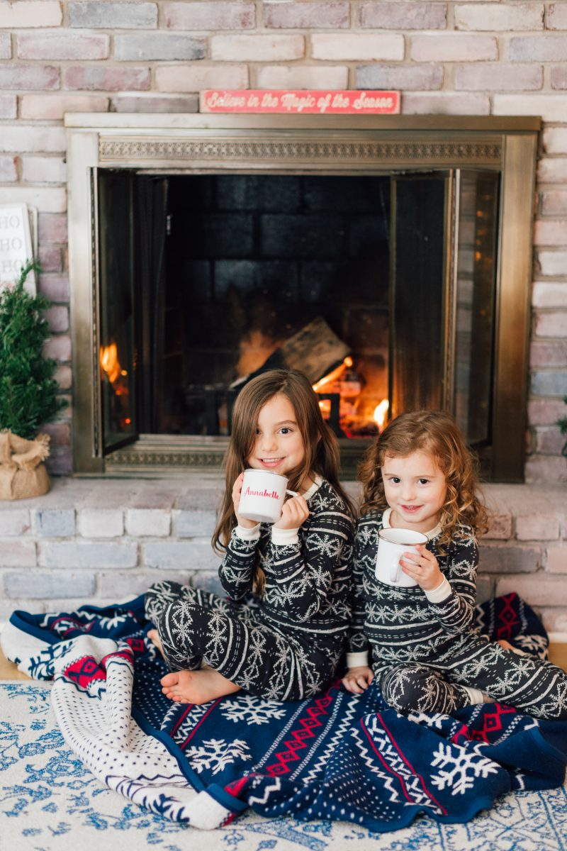 little girls drinking hot cocoa in front of fire at christmas