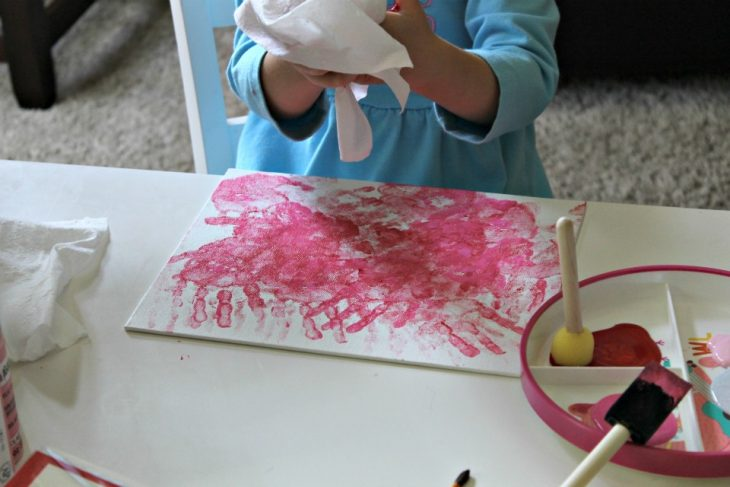 canvas with handprints in red and white with little girl cleaning paint off hands