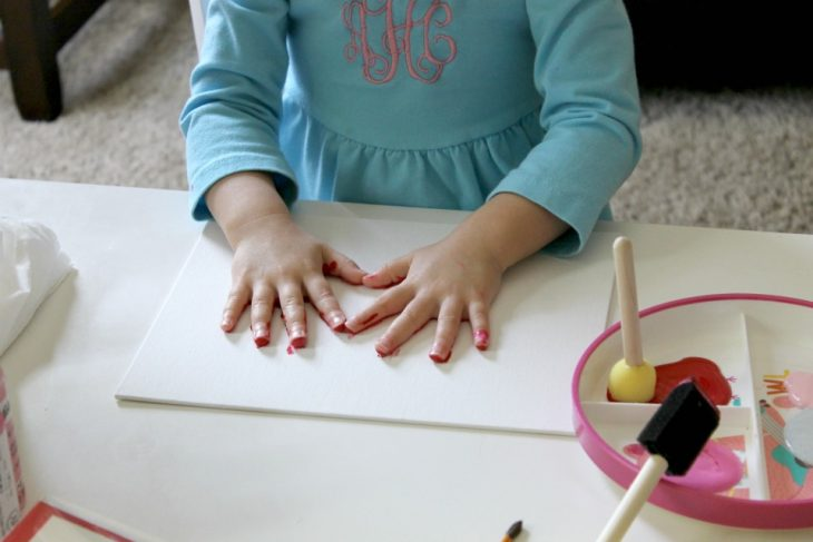 little girl placing hands in heart print shape on canvas