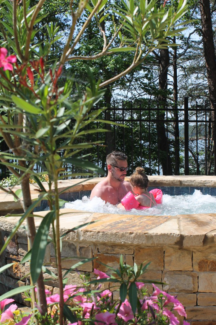 Dad in the hot tub with daughter in the sun