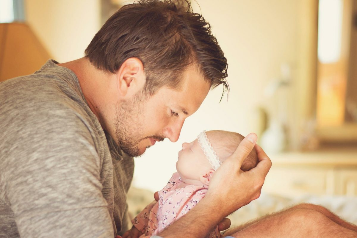 Dad wearing gray shirt holding newborn baby girl to his face