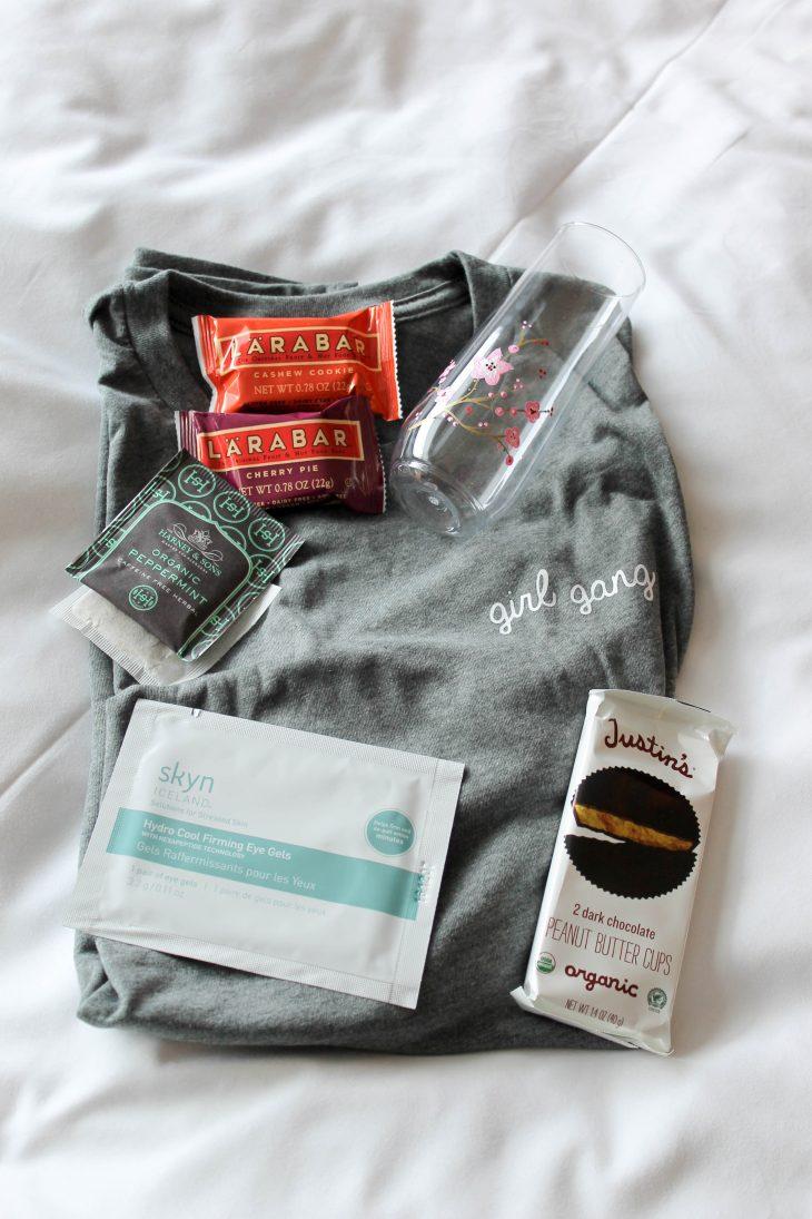 Lara bar, tea, eye patches, champagne glass, girl gang t-shirt, peanut butter cups.