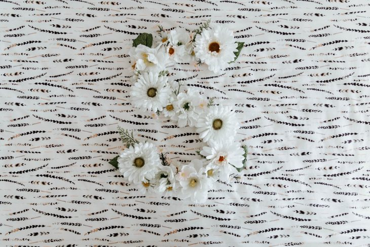 Letter S made with White Flowers on Feather Crib Sheet