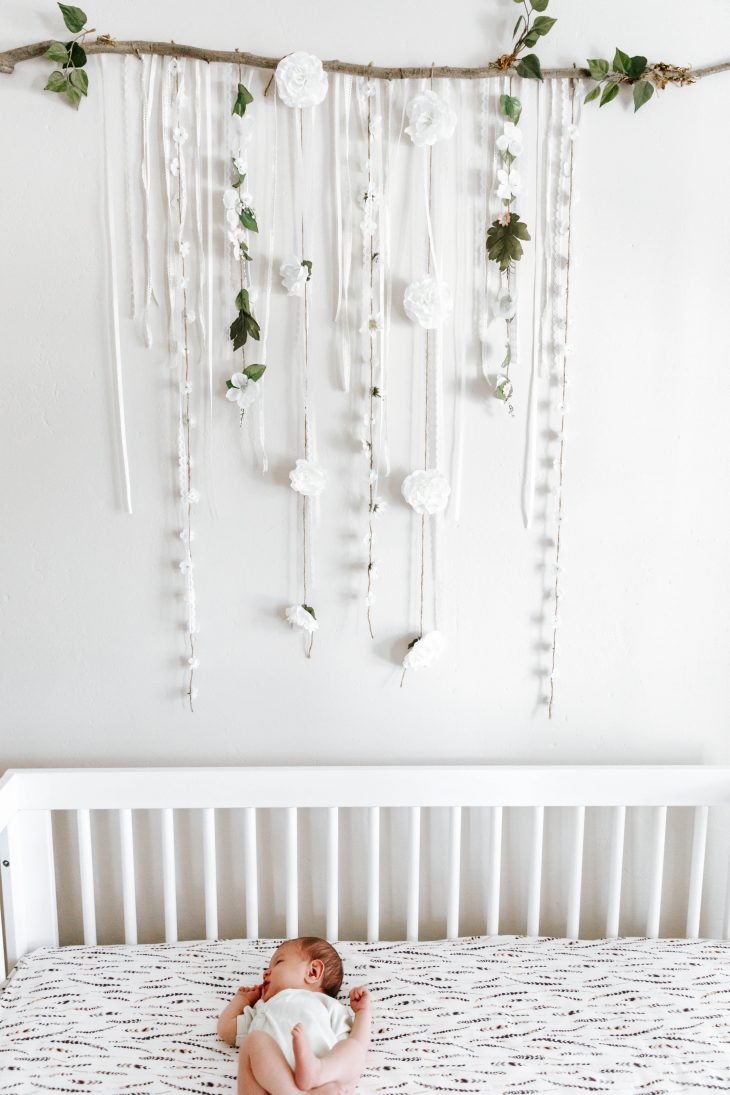 baby in white crib on feather crib sheet under white ribbon wall art