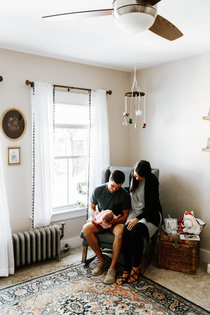 Dad holding newborn girl in arms while Mom sits beside him in gray rocker in nursery