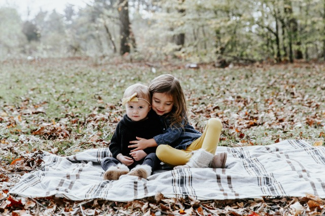 little girls hugging on a blanket on a fall day