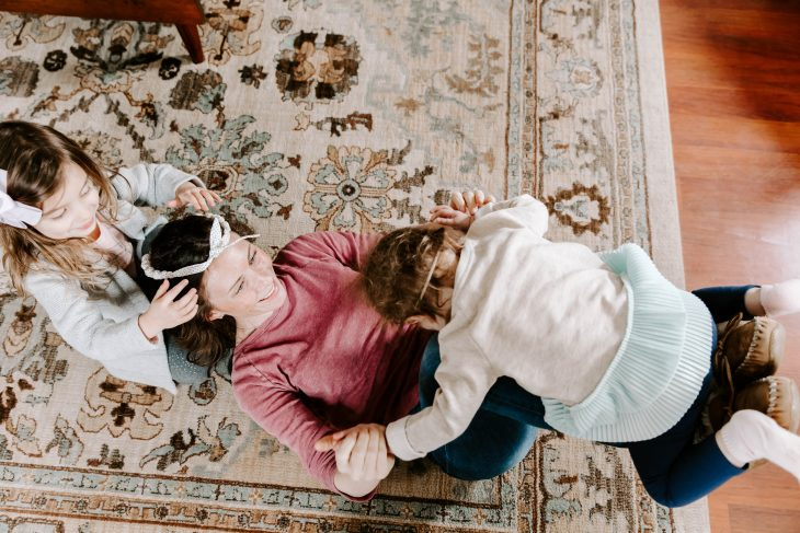 Mom and Daughters Having Fun on the Floor