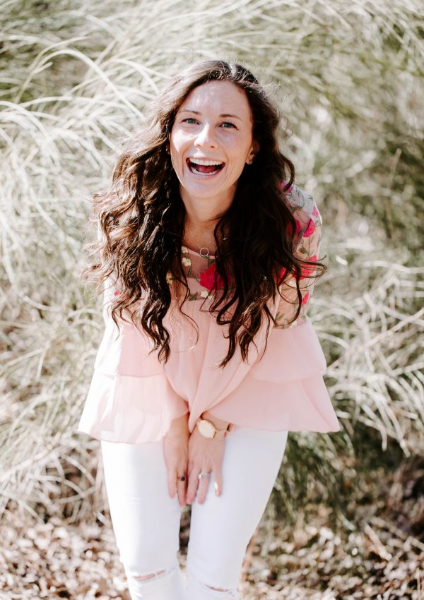laughing woman wearing a pink shirt and white jeans