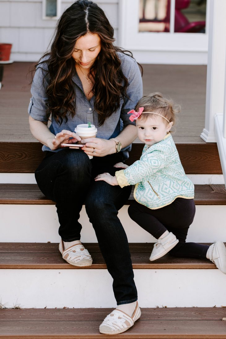 Woman holding coffee and cell phone and child