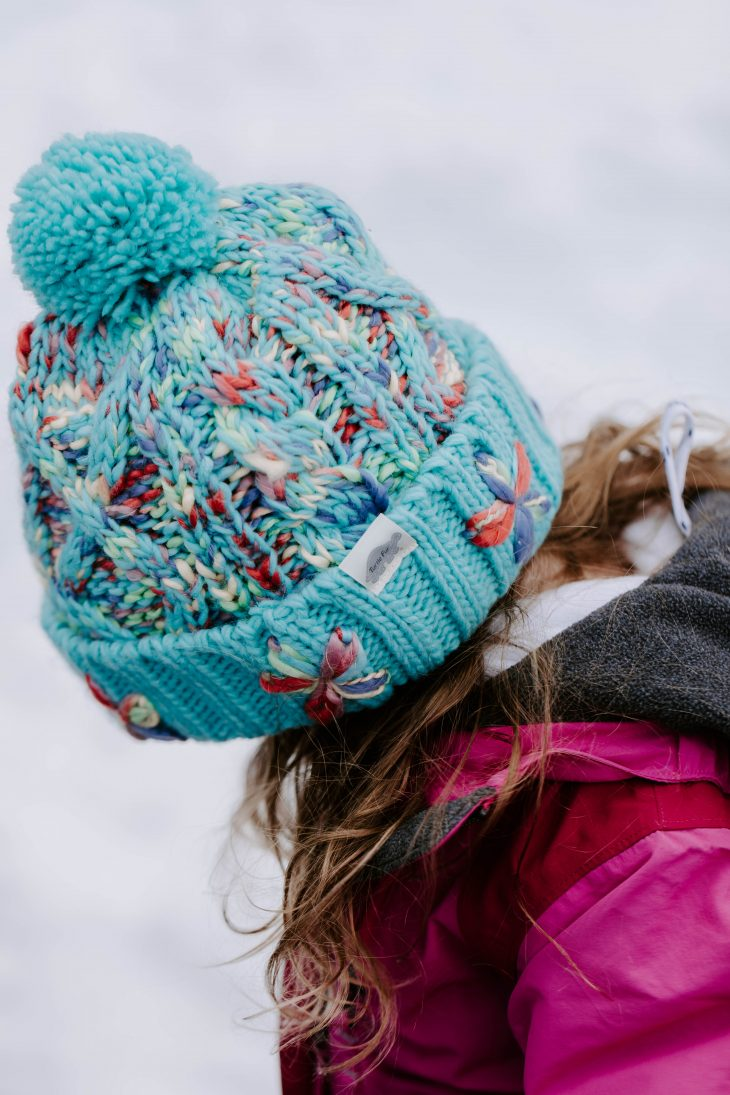 Girl wearing hand knit flower teal winter hat