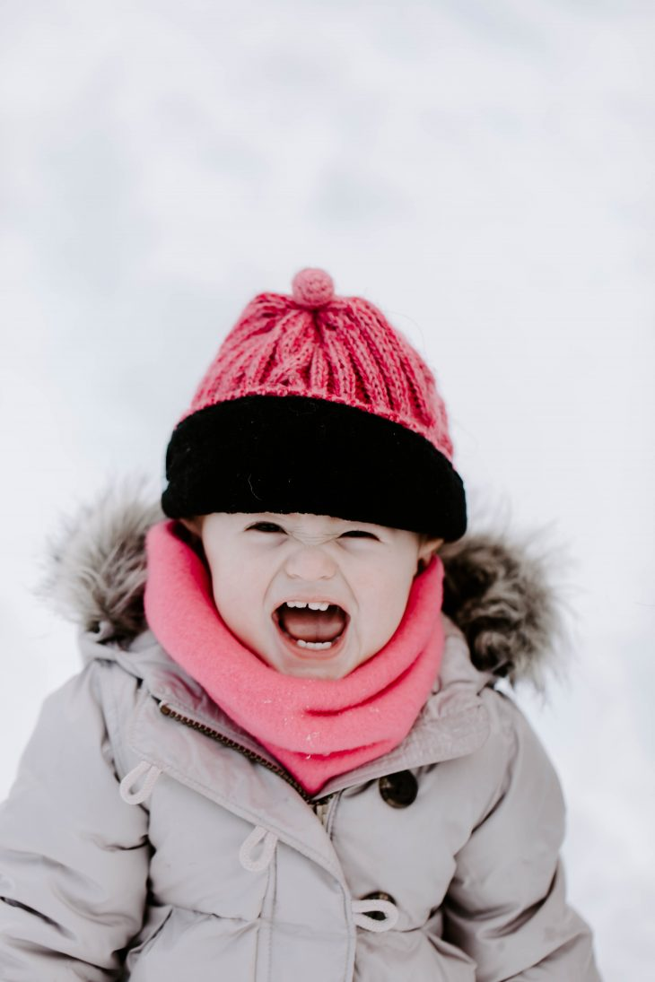 Baby smiling and laughing in the snow wearing a pink winter hat and pink neck warmer
