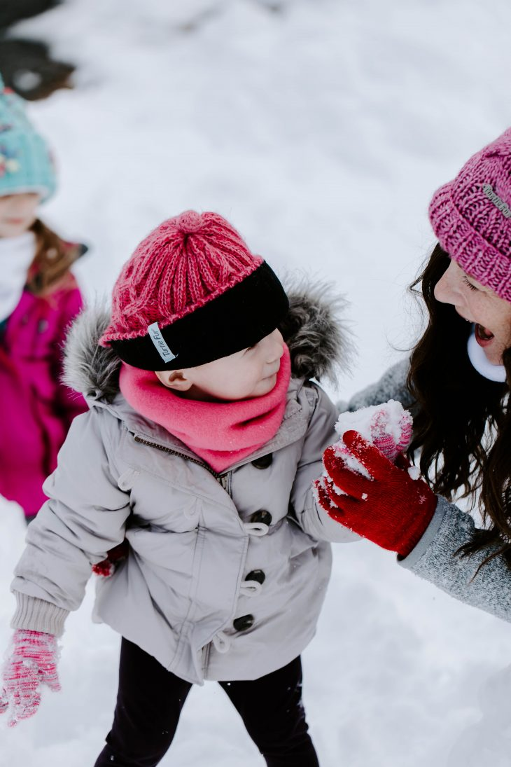 two girls and woman playing in the snow wearing snow hats