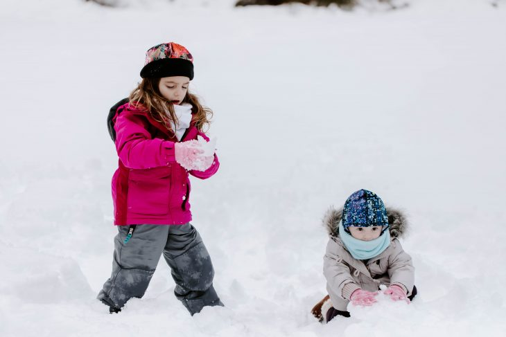 Little girl wearing pink hat, gray snow pants, pink jacket playing in the snow and toddler wearing a sun protective hat and neck warmer in the snow