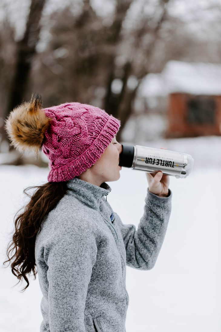 Woman wearing pink winter hat drinking water out of a silver water bottle