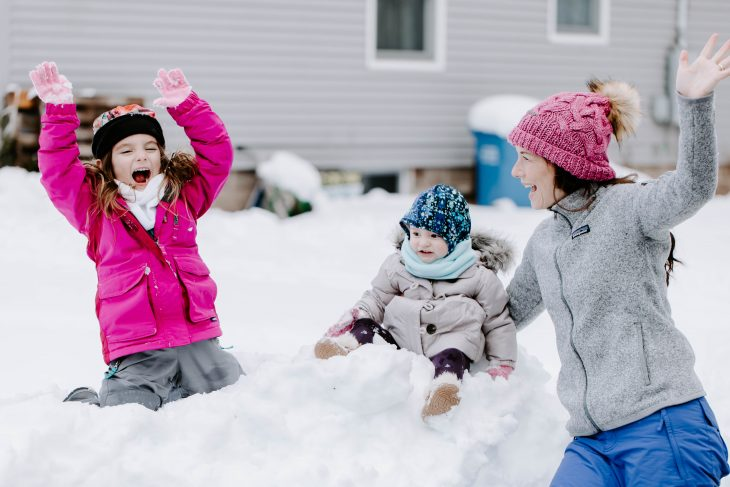 Children sitting on top of a snow mound cheering with woman