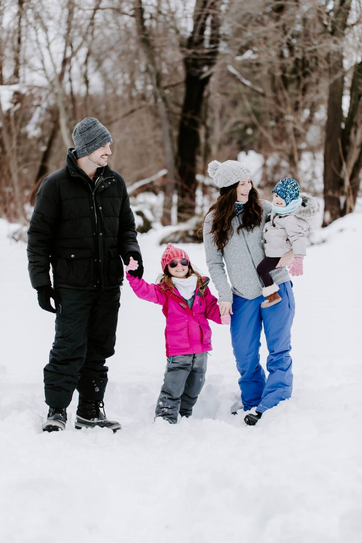 Family in the snow wearing winter jackets, winter hats, and snow pants and boots