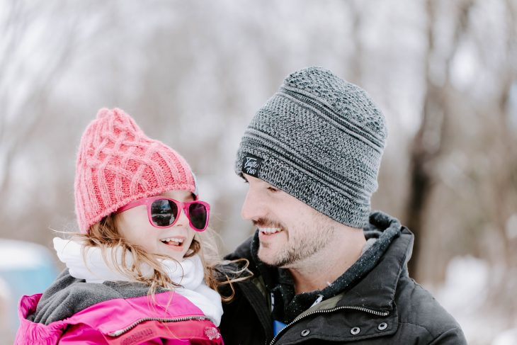 Little girl wearing pink sunglasses and a pink winter hat laughing at man wearing a gray winter hat