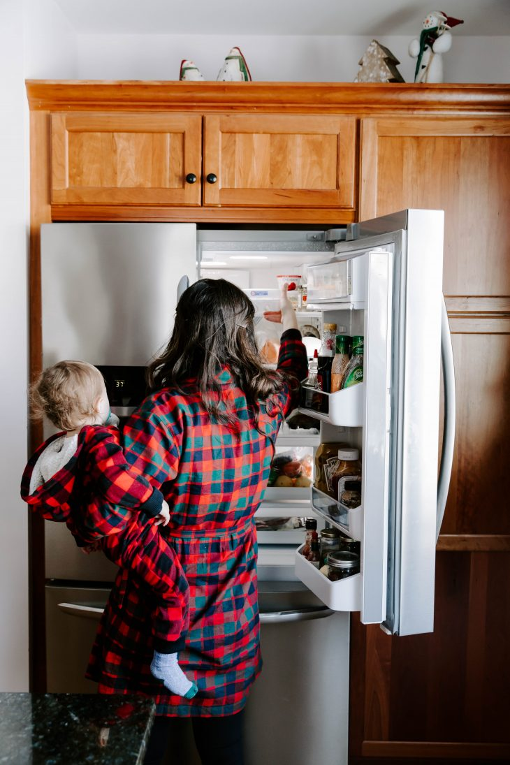 Woman looking in the fridge wearing a plaid robe while holding a baby