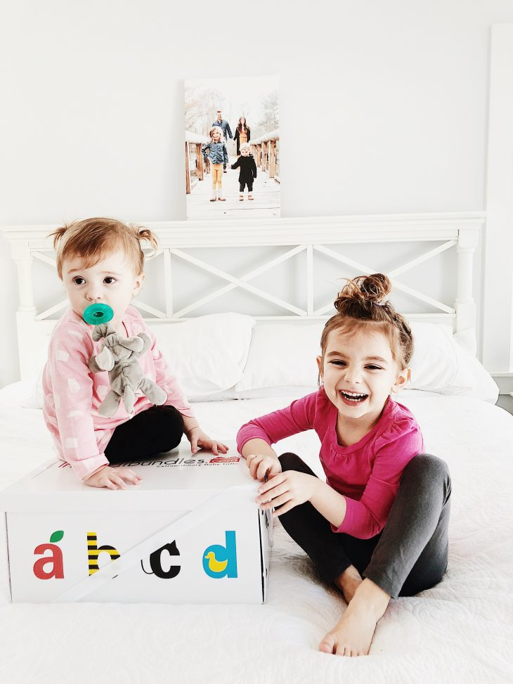 Happy kids sitting on bed with abcd box