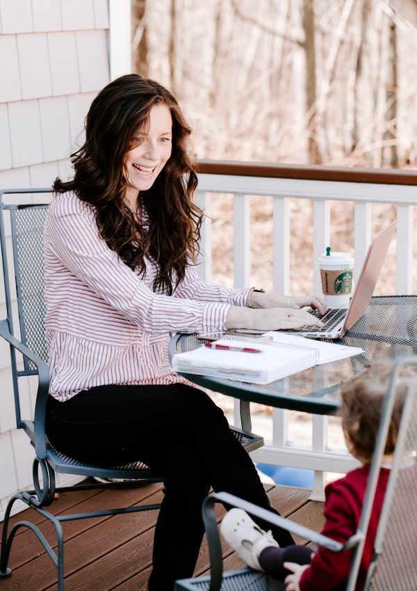 Woman at Laptop with Coffee Looking at Daughter Watching her Work
