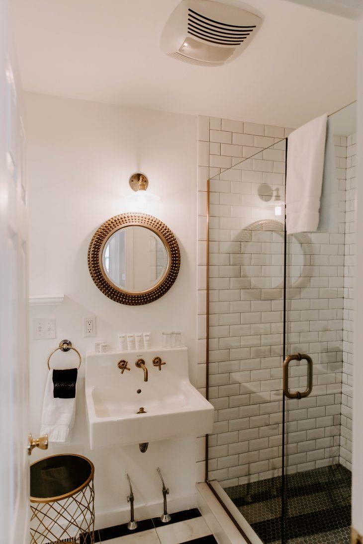 White bathroom subway tile shower gold mirror