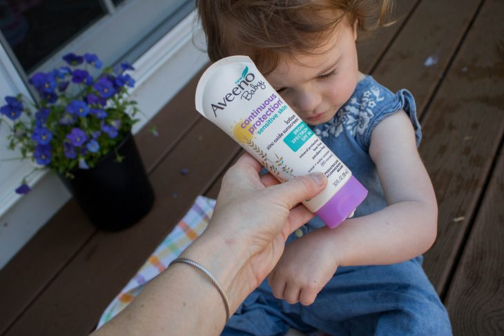 Mom applying sunscreen to baby