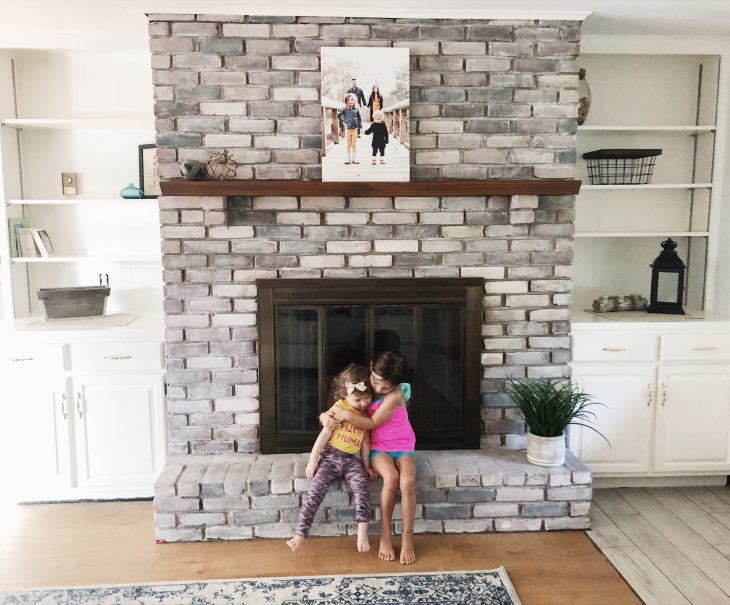 kids sitting on whitewash fireplace