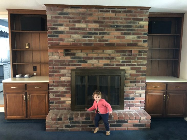 little girl sitting on brick fireplace with wood built-ins