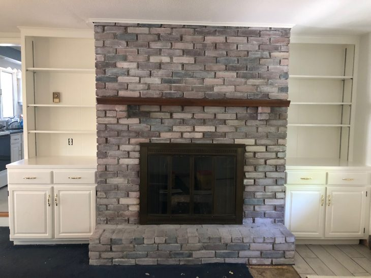 whitewash brick fireplace with white built in cabinets