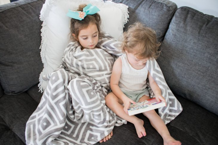 Toddlers reading stories wrapped in fleece blanket