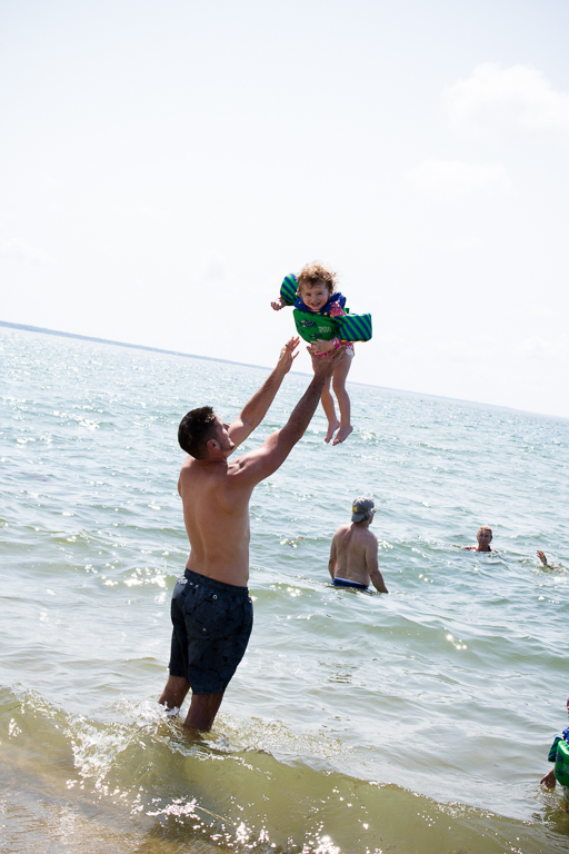 Dad tossing little girl at the beach
