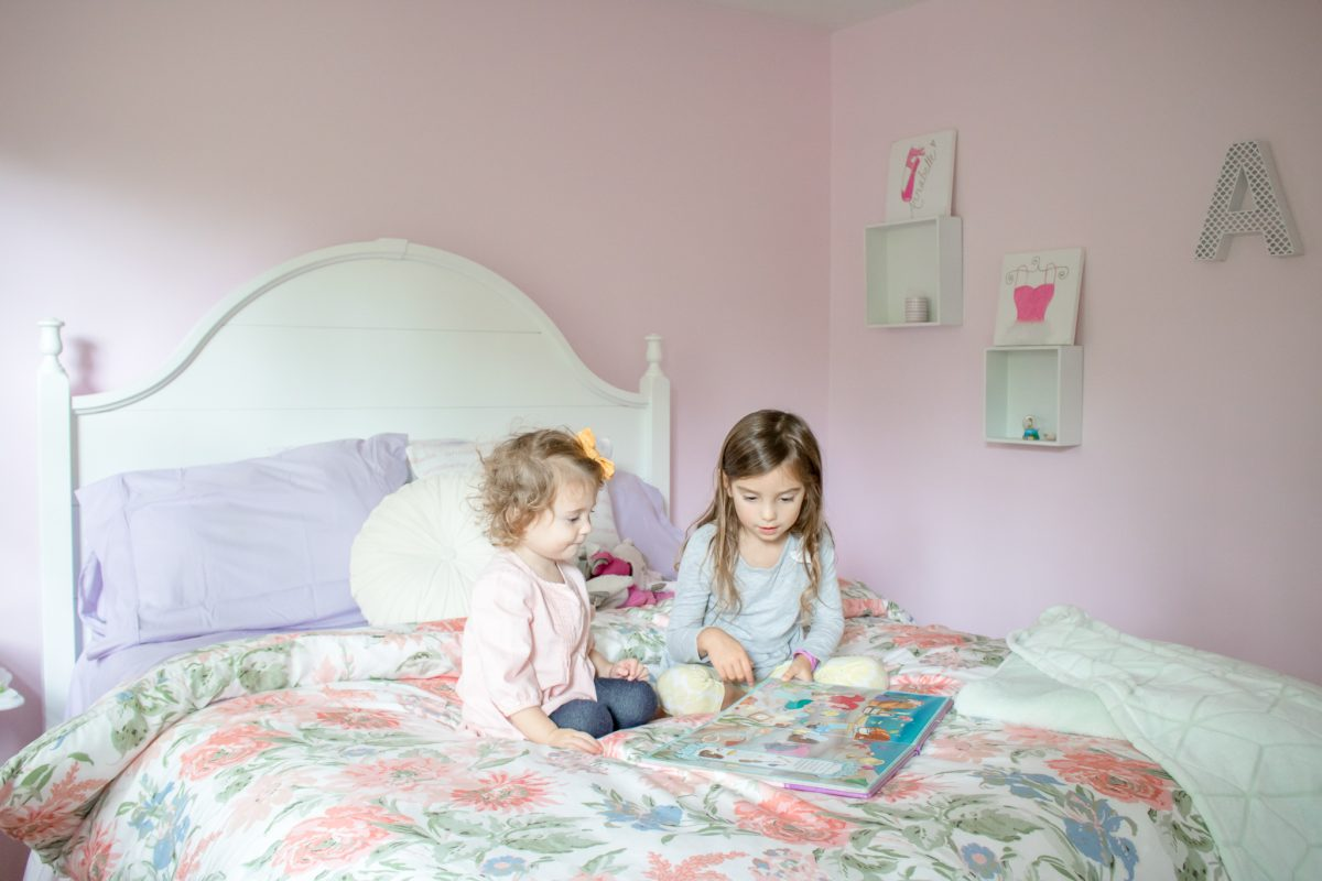 Little girls playing on top of a queen size bed with a floral comforter