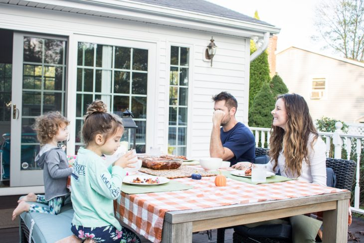 Family eating dinner together outside on deck