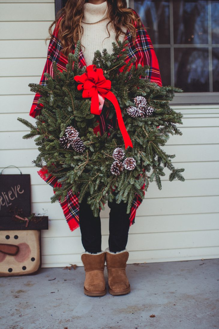 wreath with red bow, pinecones, uggs and plaid poncho