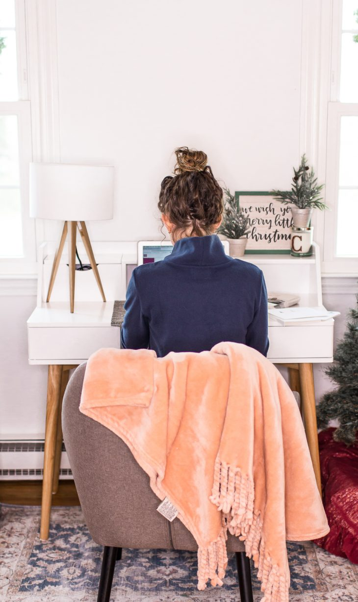 Girl Working at Computer with Pink Blanket over Gray Chair