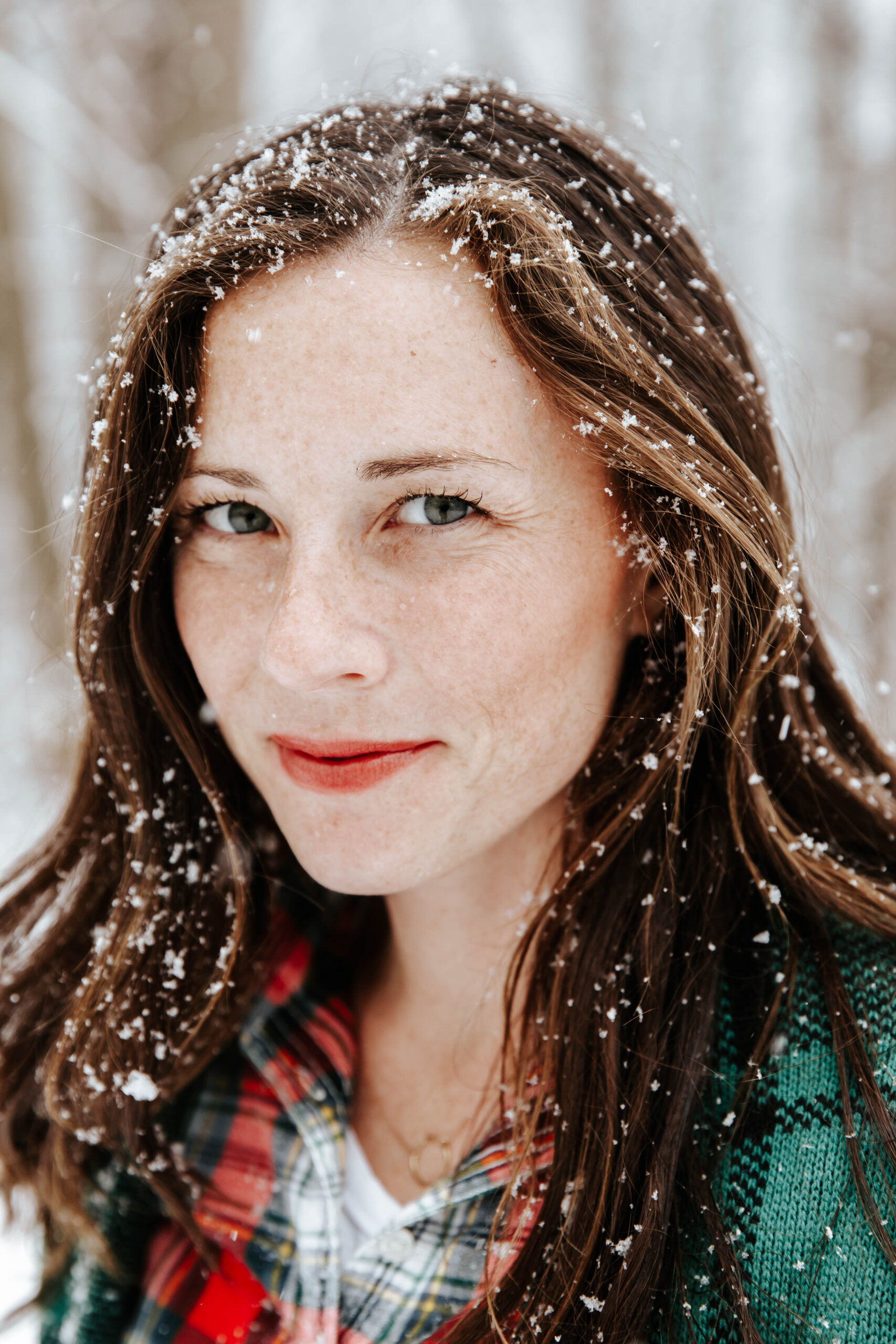woman wearing red lipstick smiling in snow
