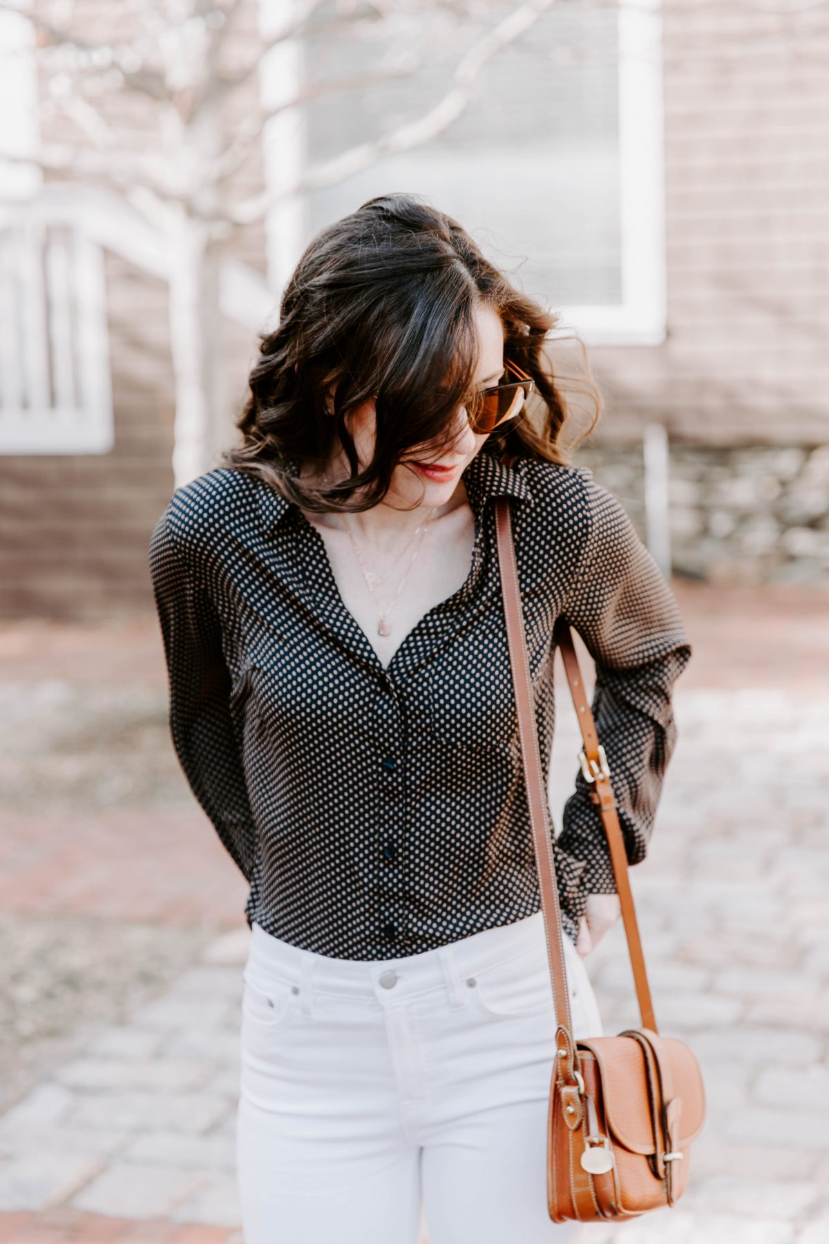 Woman wearing sunglasses, polka dot shirt, gold necklace, white pants with hands in back pockets looking to the side