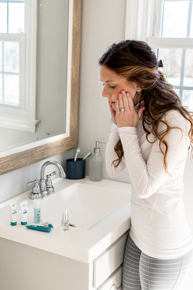 Woman in white turtleneck and gray workout pants applying face oil while standing at bathroom sink