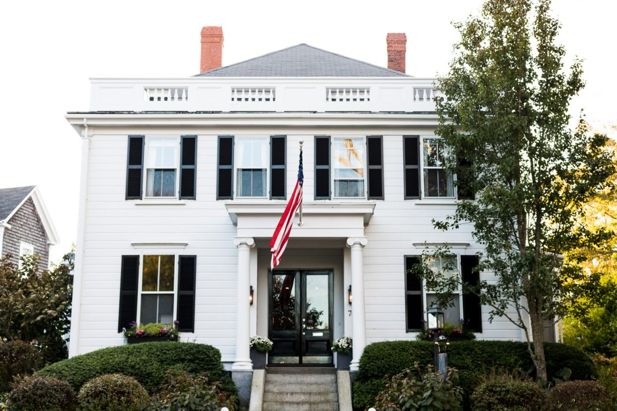 Black shutters on a white colonial style hotel in Nantucket with American Flag over entryway