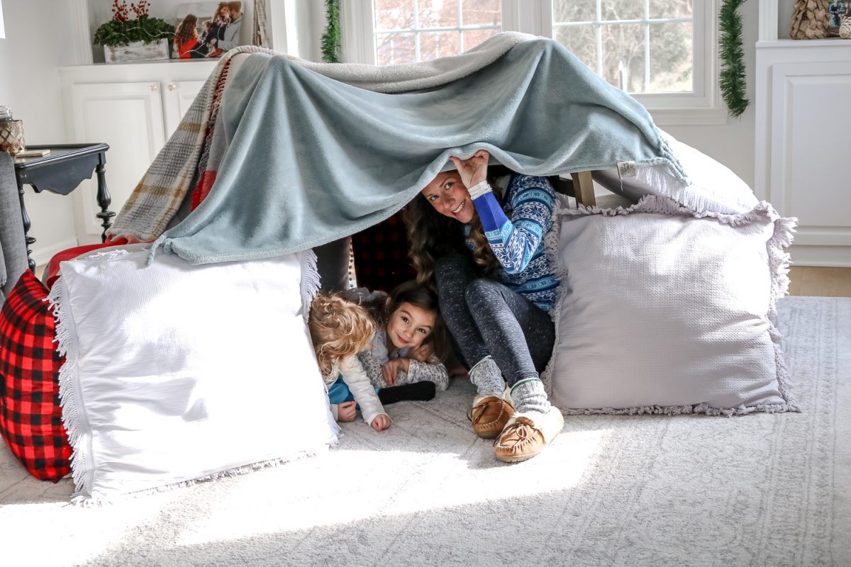 A fort made of blankets in living room with woman and little girls peeking out