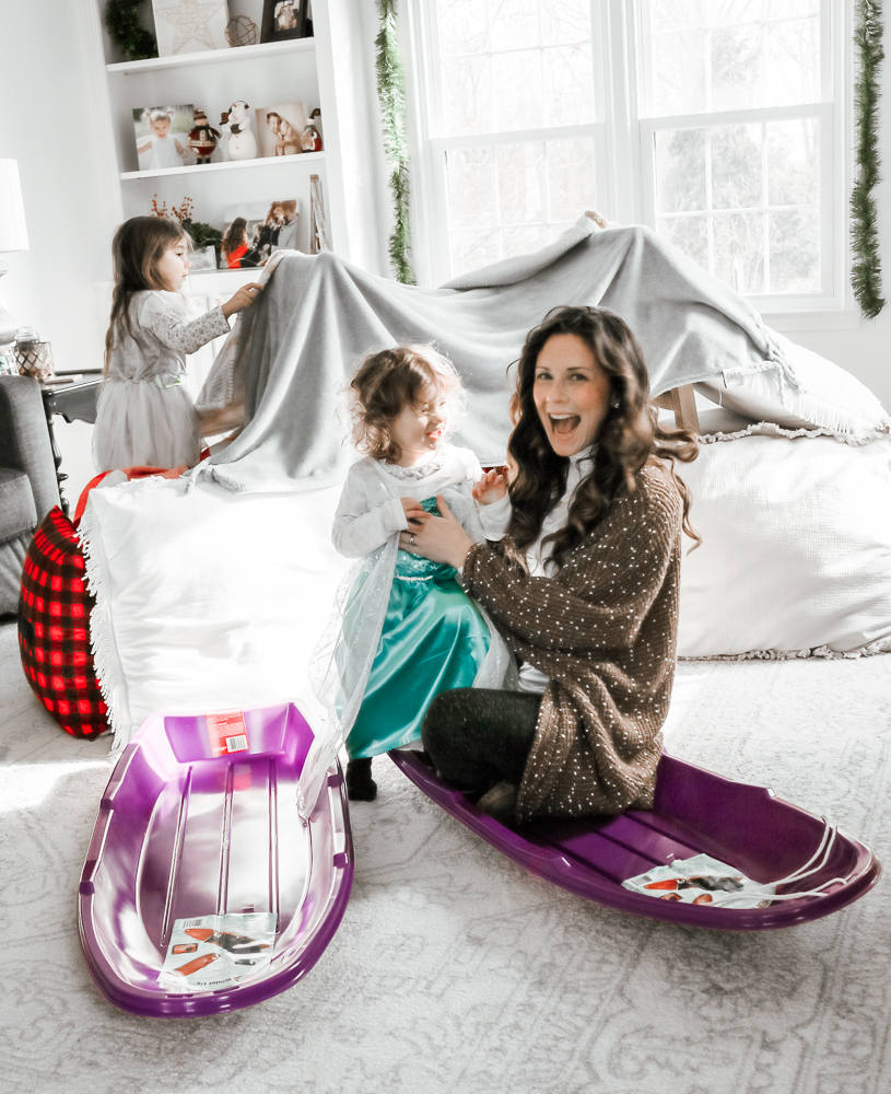 Laughing Woman sitting in plastic sled holding a laughing toddler girl wearing a costume