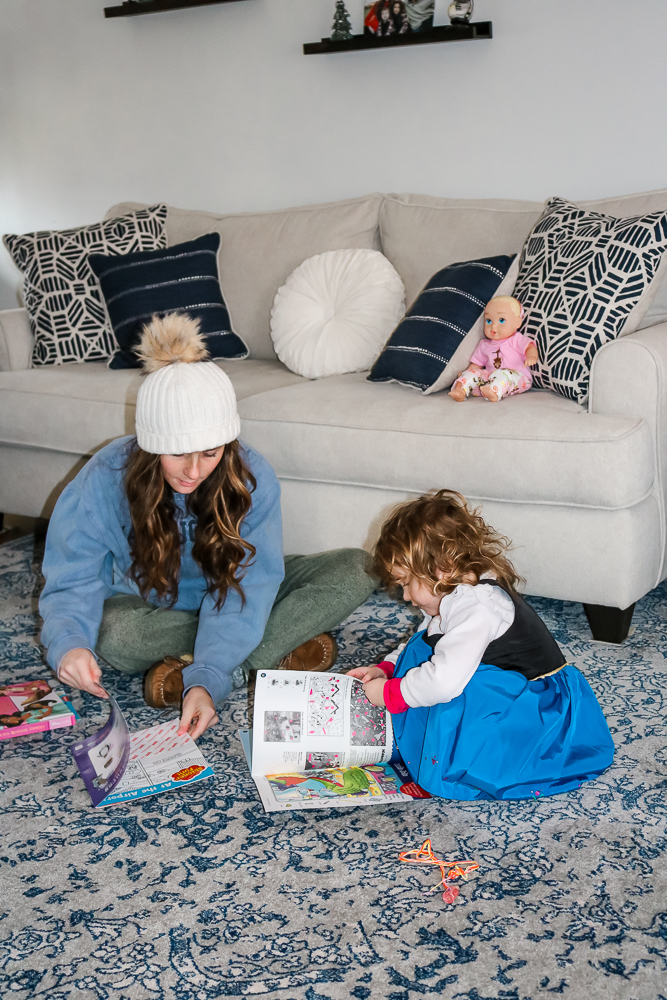 Woman wearing a white winter hat and blue sweatshirt sitting cross legged on the floor looking through a kids magazine next to a little girl wearing a costume also looking through a kids magazine