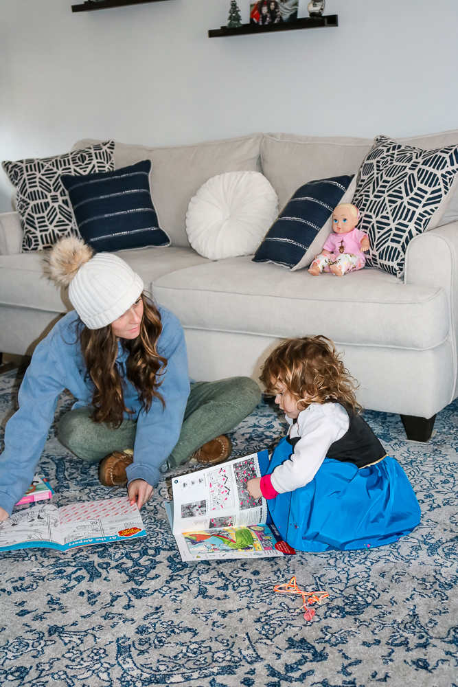 Mom wearing white winter hat with blue sweatshirt and green sweatpants playing with little girl on the floor who is wearing a blue and black dress