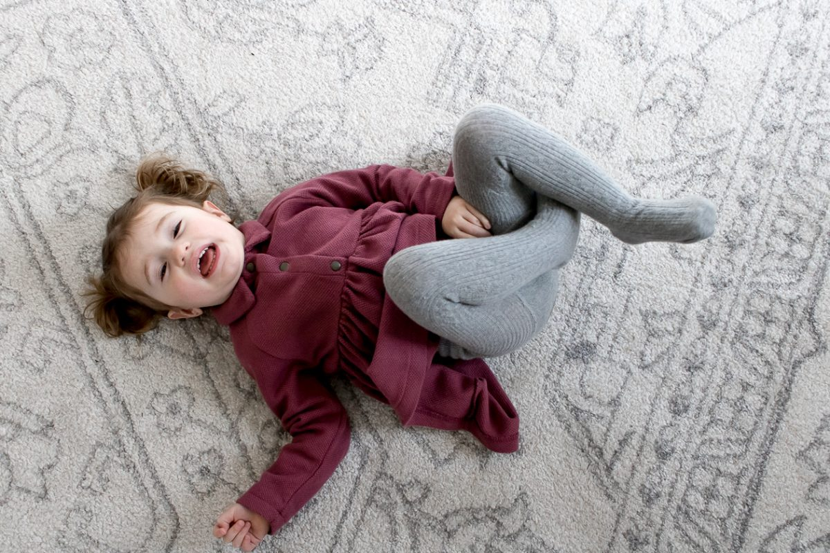 Little Girl with Pigtails in Purple Dress Smiling Laying on White Rug