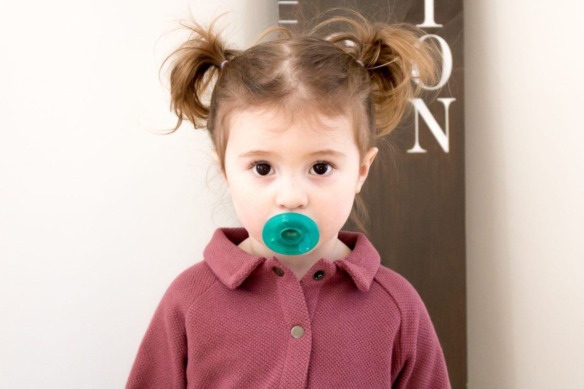 Little Girl with Pigtails in Purple Dress with Green Pacifier