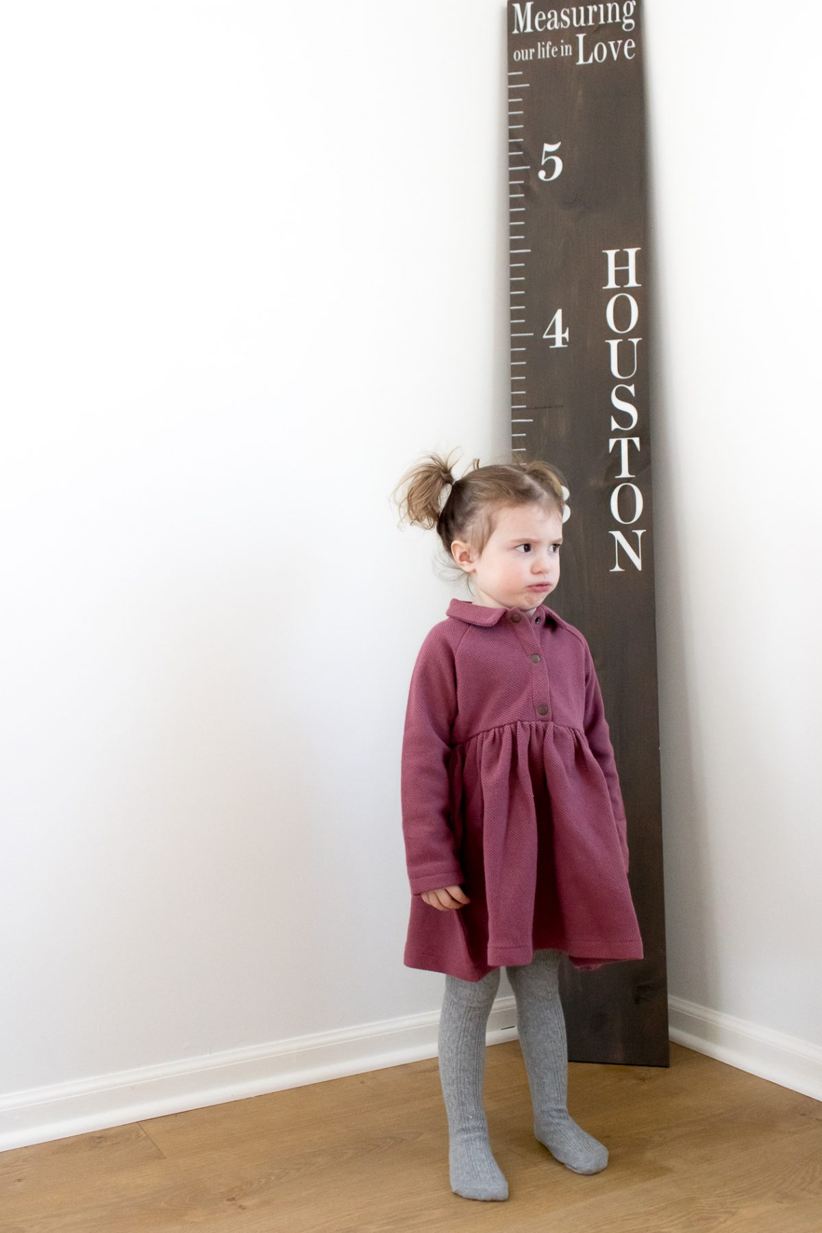 Little Girl with Pigtails in Purple Dress making a Silly Face